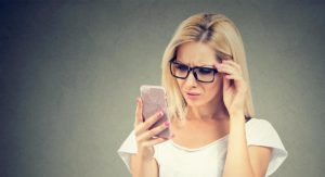 Blonde girl looking at phone confused